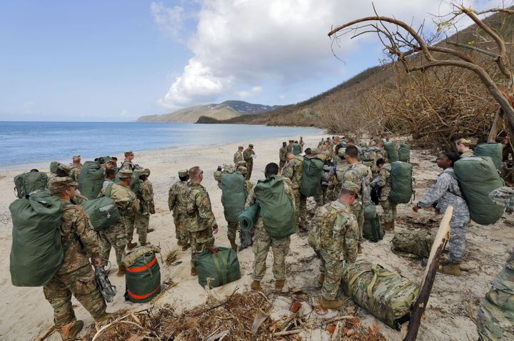 Army soldiers from the 602nd Area Support Medical Company gather on a beach as they await transport on a Navy landing craft w