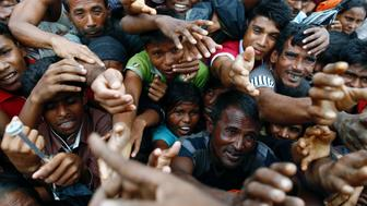 Rohingya refugees stretch their hands to receive aid distributed by local organisations at a makeshift camp in Cox's Bazar, Bangladesh September 18, 2017. REUTERS/Danish Siddiqui