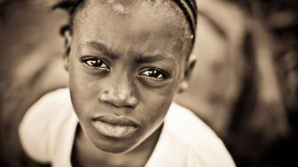 A young African girl gazing at the camera with a serious expression.