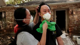 "Vera Hsiung cleans off her husband, Elliot Wu's, neck and face as they clean out their home which was flooded with water for twelve days in the aftermath of tropical storm Harvey in west Houston, Texas, U.S. September 11, 2017. ""We're really worried about contacting disease from exposure to mold,"" said Hsiung.  Their home flooded after controlled releases from Addicks Reservoir and neighboring Barker reservoir. REUTERS/Chris Aluka Berry"