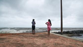People look at the ocean on September 18, 2017, in Basse-Terre, on the Fench Caribbean island of Guadeloupe, as Hurricane Maria approaches the Caribbean.  Hurricane Maria strengthened rapidly on September 18 as it blasted towards the eastern Caribbean, forcing exhausted islanders -- still recovering from megastorm Irma -- to brace for the worst again. The US National Hurricane Center (NHC) said the 'major hurricane' had intensified to Category 3 as it approached the French island of Guadeloupe, the base for relief operations for several islands devastated by Irma this month.   / AFP PHOTO / Cedrick Isham CALVADOS        (Photo credit should read CEDRICK ISHAM CALVADOS/AFP/Getty Images)
