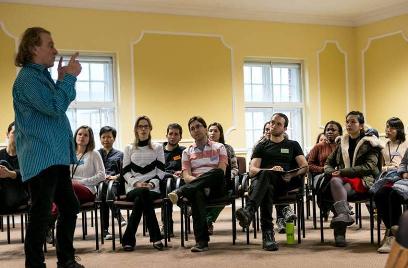 A music teacher talking to a gathering of Cumberland, Cambridge Trust and Chevening Scholars