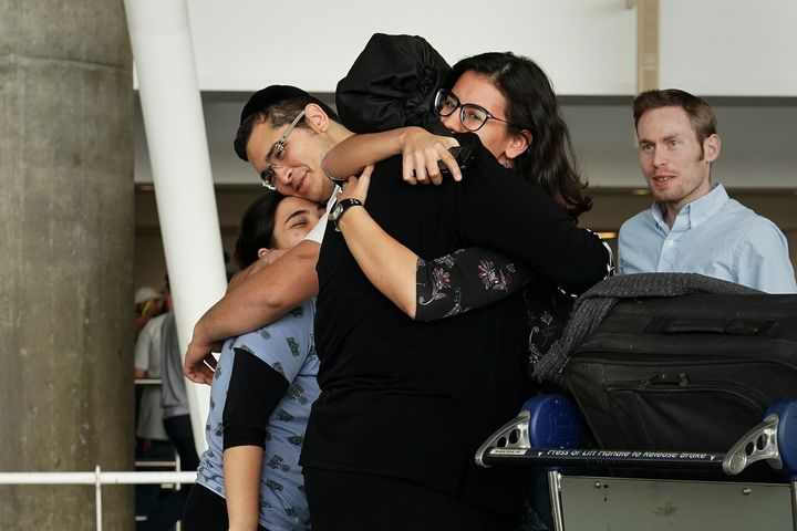 People hug after arriving in advance of the travel ban to the U.S. at John F. Kennedy airport in New York City, on June