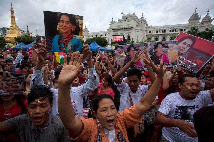 People hold the Myanmar national flag and placards as they attend a public gathering to listen to the live speech of Myanmar'