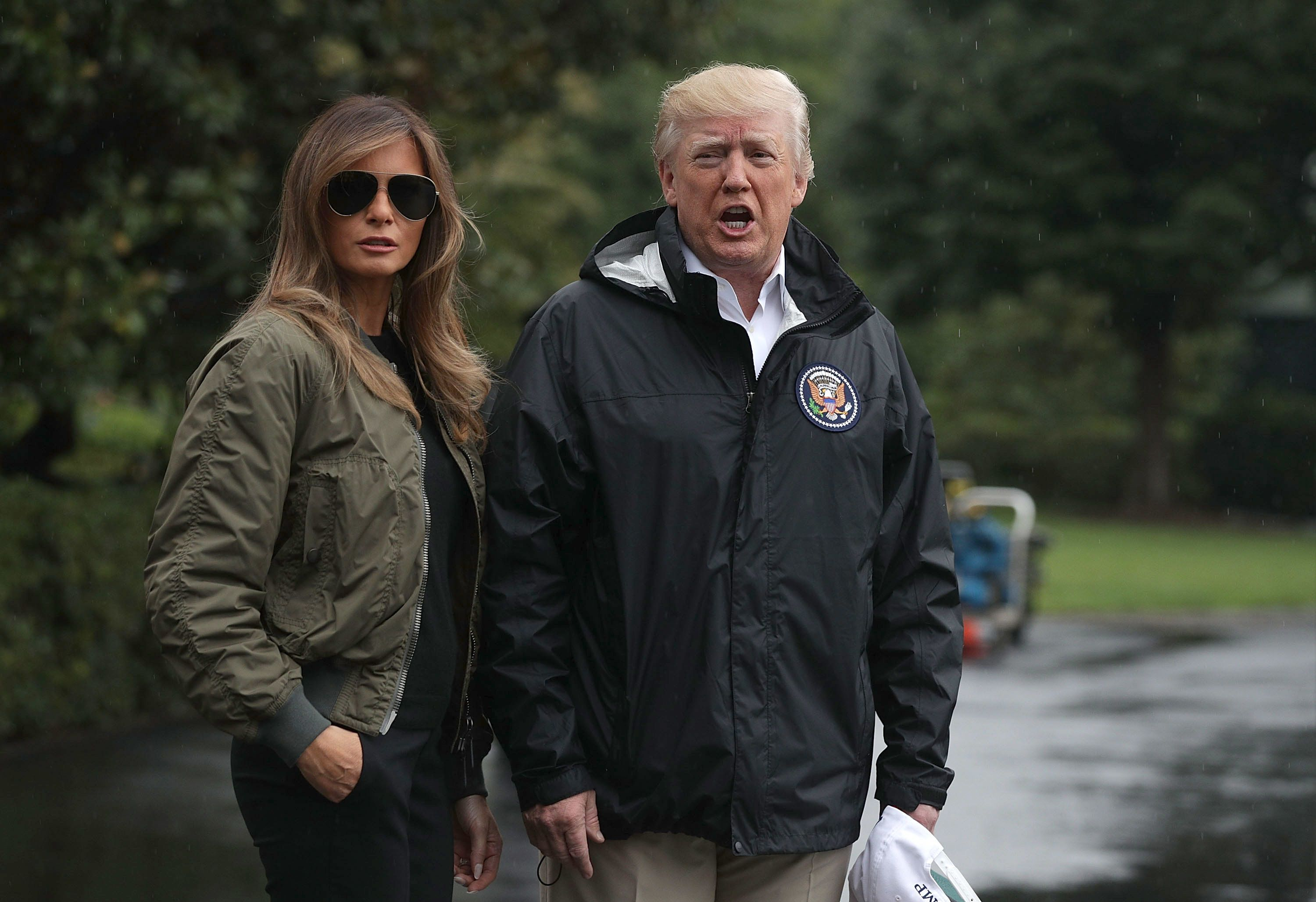 WASHINGTON, DC - AUGUST 29:  U.S. President Donald Trump speaks to members of the media briefly as first lady Melania Trump looks on prior to their Marine One departure from the White House August 29, 2017 in Washington, DC. President Trump was traveling to Texas to observe the Hurricane Harvey relief efforts.  (Photo by Alex Wong/Getty Images)