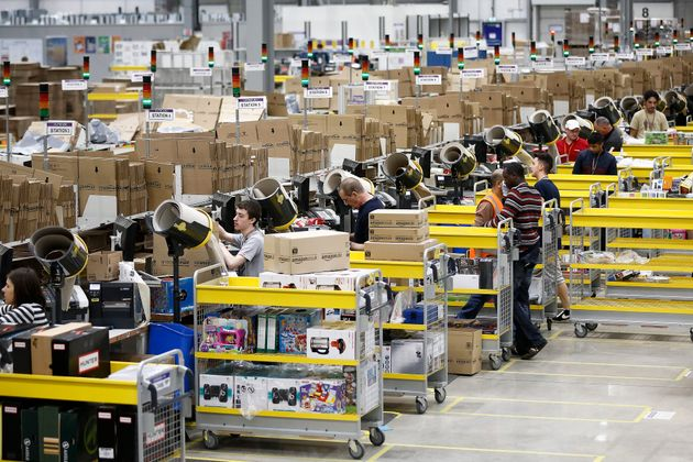 Staff at Amazon's Rugeley site work at 'packing' stations in the vast warehouse (pictured in