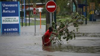 A man removes a branch in a flooded street after the passage of Hurricane Maria in Pointe-a-Pitre, Guadeloupe island, France, September 19, 2017. REUTERS/Andres Martinez Casares