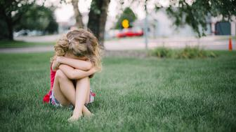 Little girl with curly hair sits on grass and cries into her arms.