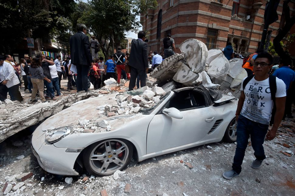 A man stands next to a car crushed by debris from a damaged building after a quake rattled Mexico City on Tuesday.