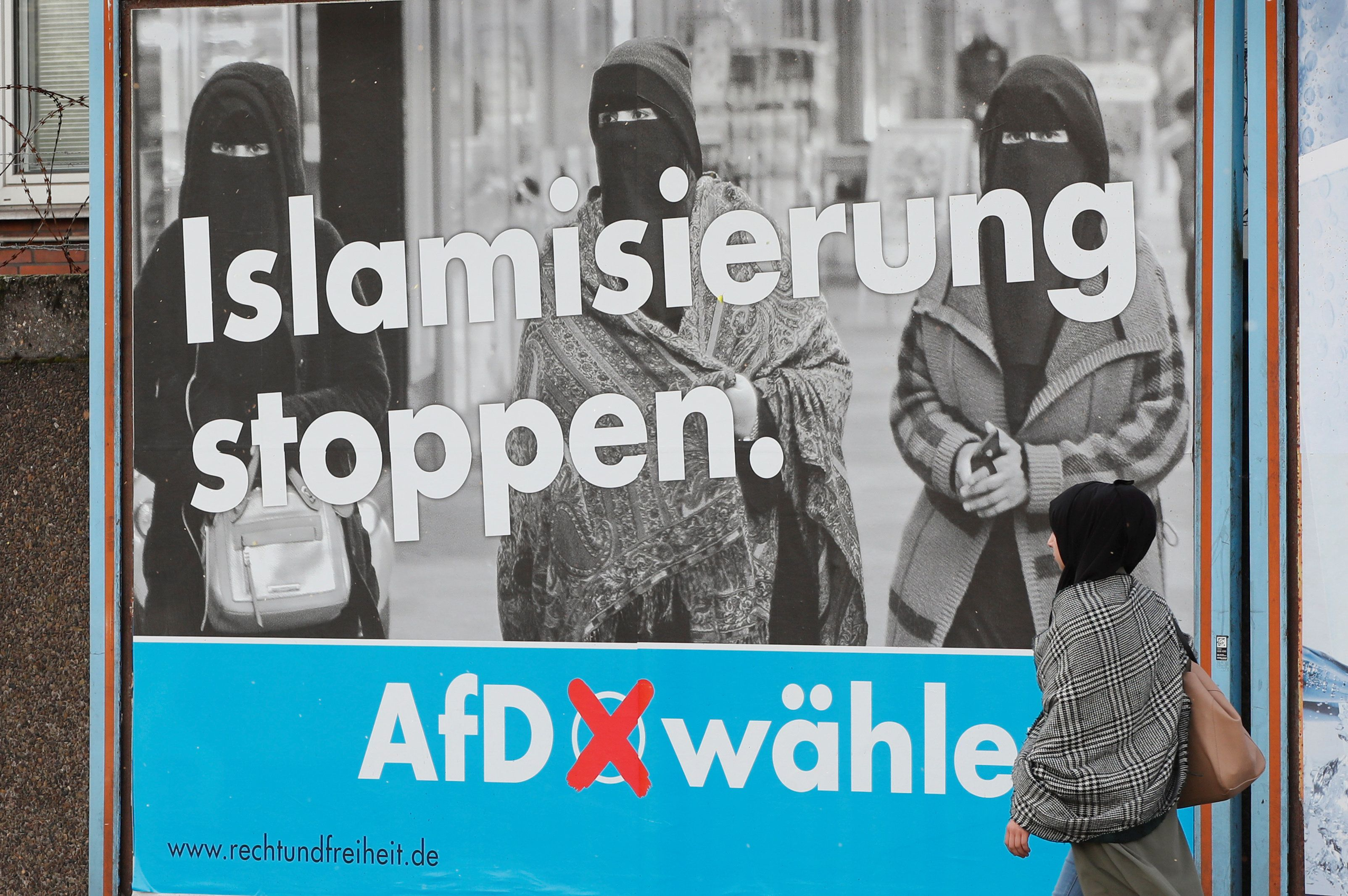 A woman with a headscarf walks past an election campaign poster of the anti-immigration party Alternative fuer Deutschland AfD, in Marxloh, a suburb of Duisburg which local media said is populated mostly with people of Turkish migrant background, Germany September 13, 2017. REUTERS/Wolfgang Rattay