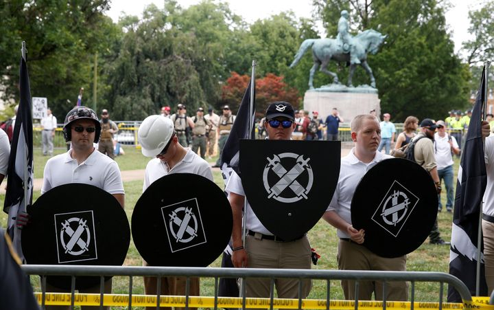 White supremacists, holding shields with a symbol of Vanguard America on them, gather under a statue of Robert E. Lee during