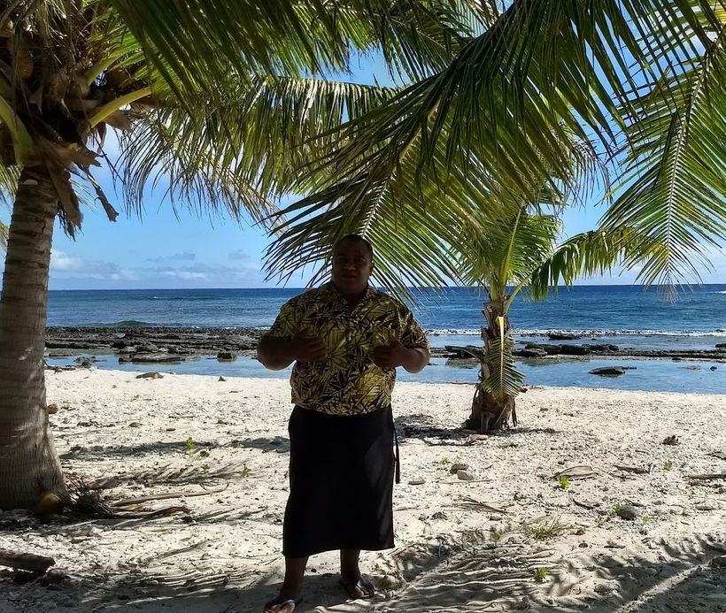Chief Aeau lamenting on decline in coral health on reef behind him in his village.