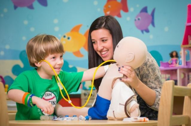 <p>St. Jude patient Griffin plays doctor with a medical doll alongside his child life specialist. (2016)</p>