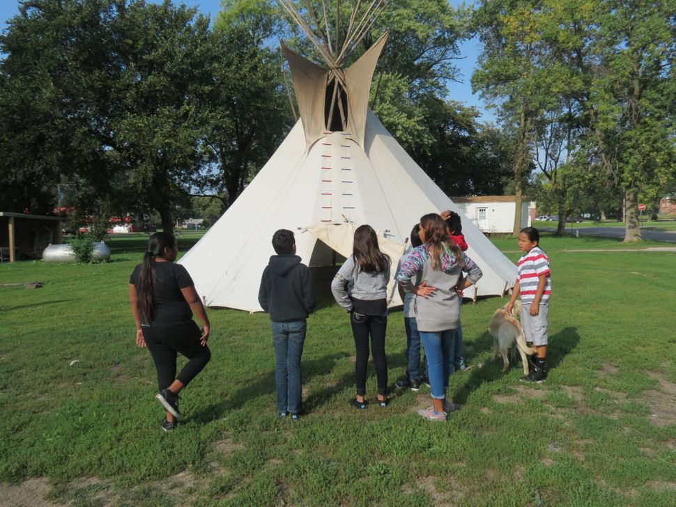 A middle school class from Umonhon Nation Public School, out on a cultural experience in the community, learning about the ti