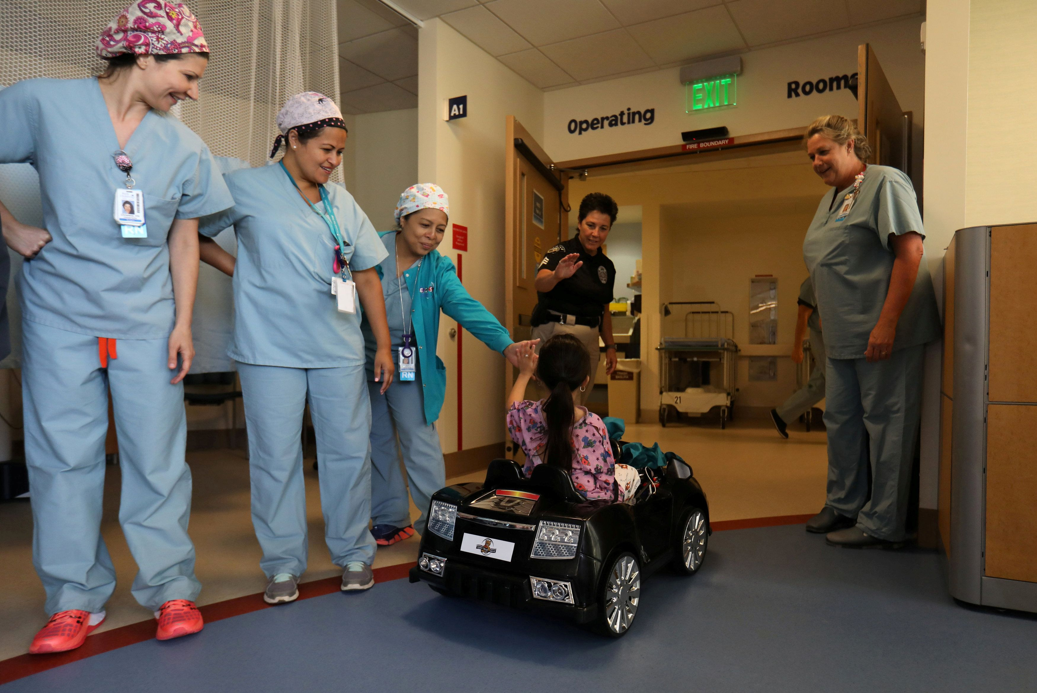 Andrea Destraio, 5, slaps hands with medical staff and invited police officers whose charity donated to Rady Children's Hospital to start a program that uses remote control cars to take young patients to the operating room, in San Diego, California, U.S. September 19, 2017.     REUTERS/Mike Blake     TPX IMAGES OF THE DAY