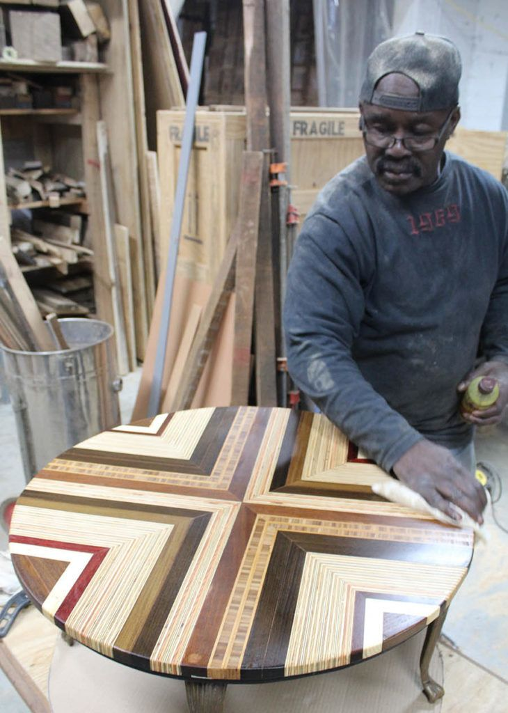 Former inmate Gene Manigo puts the finishing touches on a table he created as part of the Refoundry initiative.