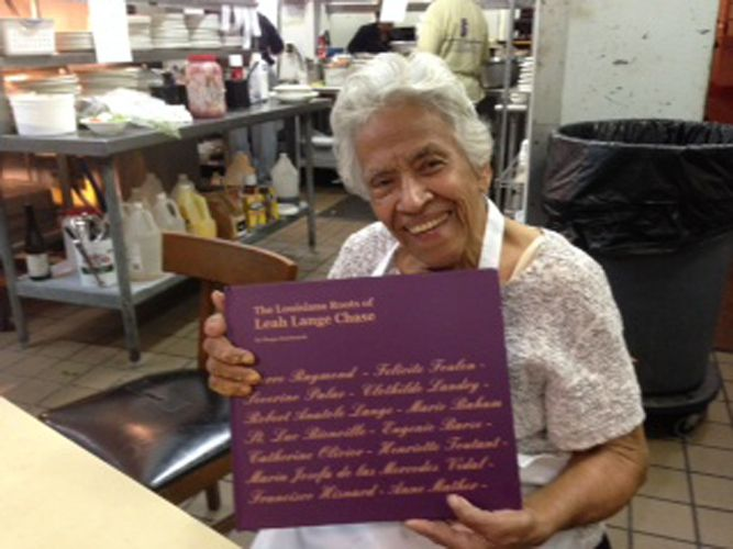 <em>Leah Chase holds book of her family history in her personal kitchen in Dooky Chase's</em>
