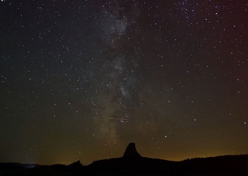 Devil's Tower rises like a silent sentinel above the surrounding Wyoming wilderness. The Milky Way descends through it...