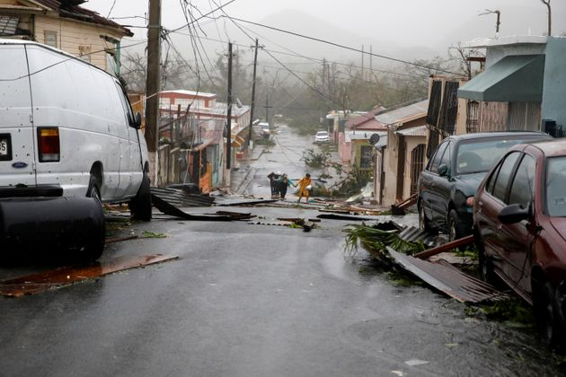 People walk on the street next to debris after the area was hit by Hurricane Maria in Guayama, Puerto...