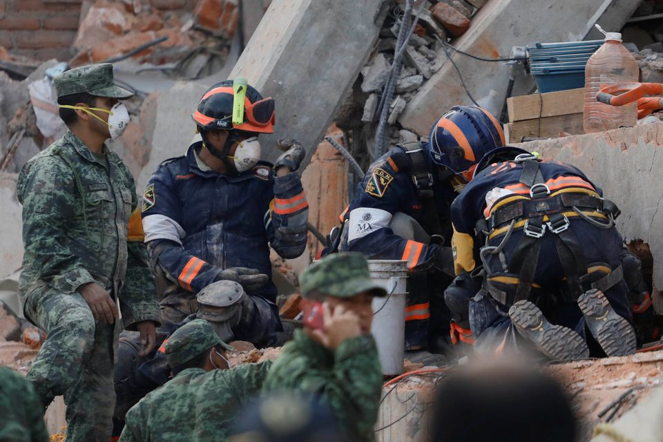 Rescue workers search for students through the rubble after an earthquake at Enrique Rebsamen school...