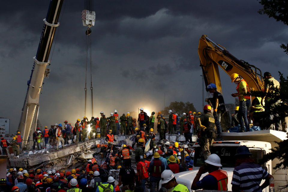 Rescue workers and Mexican soldiers take part in a rescue operation at a collapsed building after an...