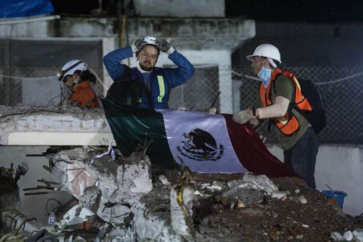 First responders place a Mexican flag over a collapsed building in Mexico City.