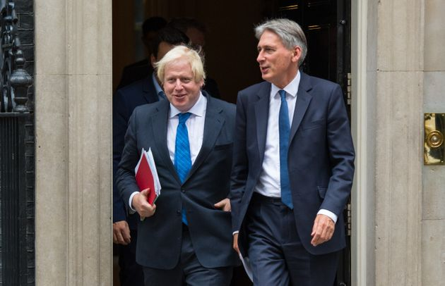 Boris Johnson (left) and Chancellor Philip Hammond leave 10 Downing Street side by side in a show of