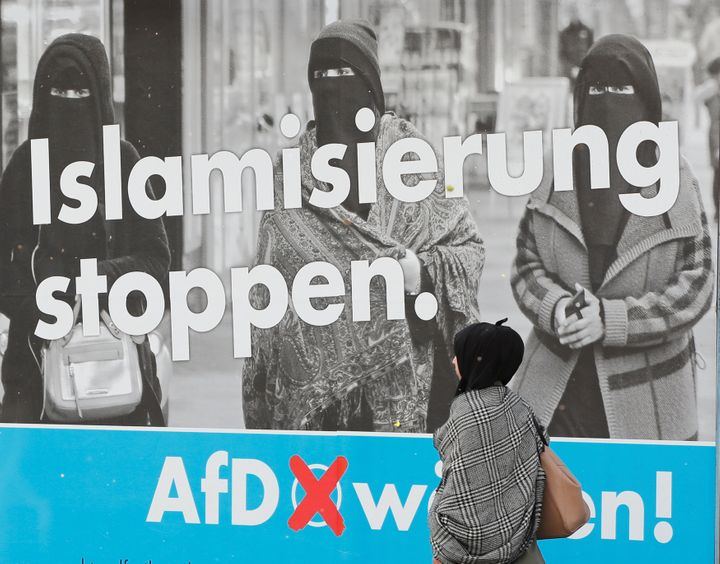 A woman with a headscarf walks past an AfD campaign poster in Marxloh, a suburb of Duisburg, Germany, in which many people ha