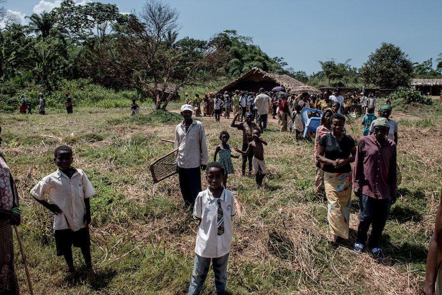 Moradores de Uma saem de um centro comunitário depois de uma reunião com médicos