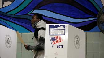 A voter carries his ballot behind a ballot booth during the U.S. presidential election at a polling station in the Bronx Borough of New York, U.S., November 8, 2016. REUTERS/Saul Martinez