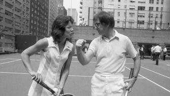 Wimbledon champion Billie Jean King tactfully holds down the net, so that 55-year-old Bobby Riggs can easily clear it during meeting at an east side tennis club here July 11th. Returning in triumph from London, Mrs. King will meet Riggs in a $100,000 winner-take-all tennis match, it was announced July 11th.