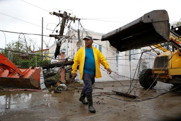 Workers use backhoe loaders to remove damaged electrical installations from a street in Salinas, Puerto...