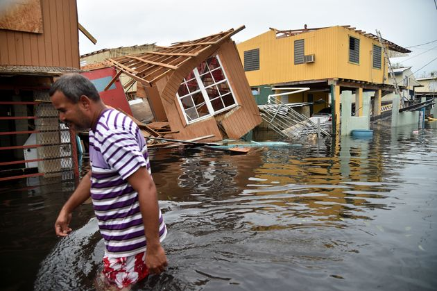 A man walks past a house lying in floodwater in Catano town in Juana Matos, Puerto Rico, on Sept. 21,