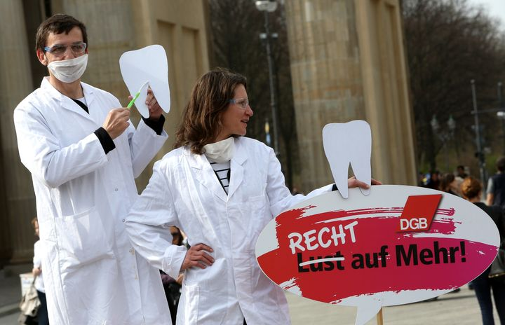 Two demonstrators posing as unequally paid dentists, the woman holding a sign reading 'Not a Wish But a Right to More!', demo