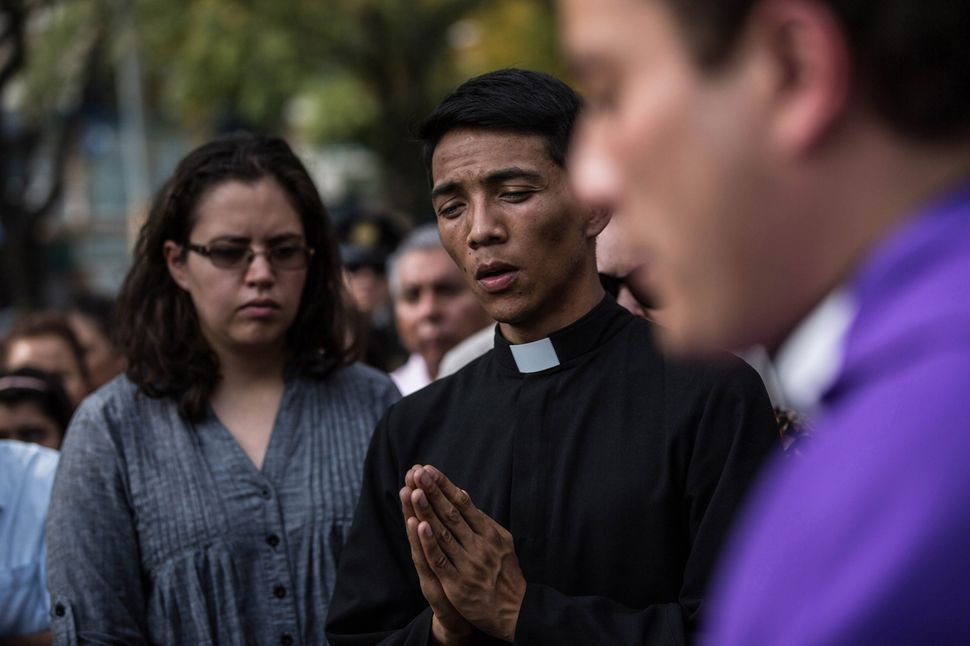 Relatives and friends of victims attend a catholic mass outside the the Enrique Rebsamen school that collapsed during Tuesday