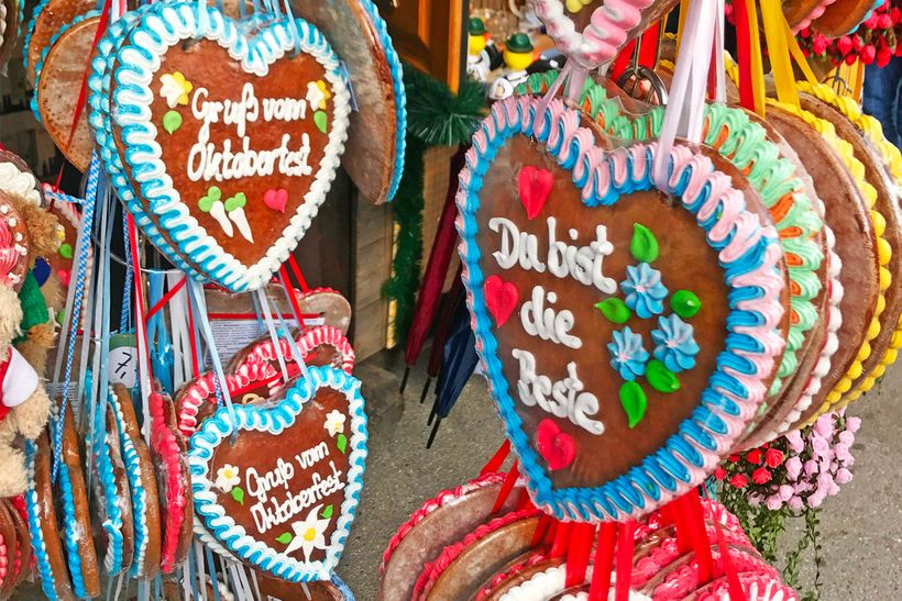 "Lebkuchenherzen (gingerbread hearts) necklaces on display with different phrases from saucy sayings to ""I love you.&quot"