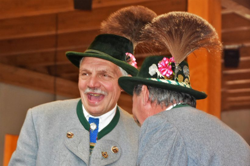 Two men talking wearing the traditional Bavarian Gamsbart hunting hats.