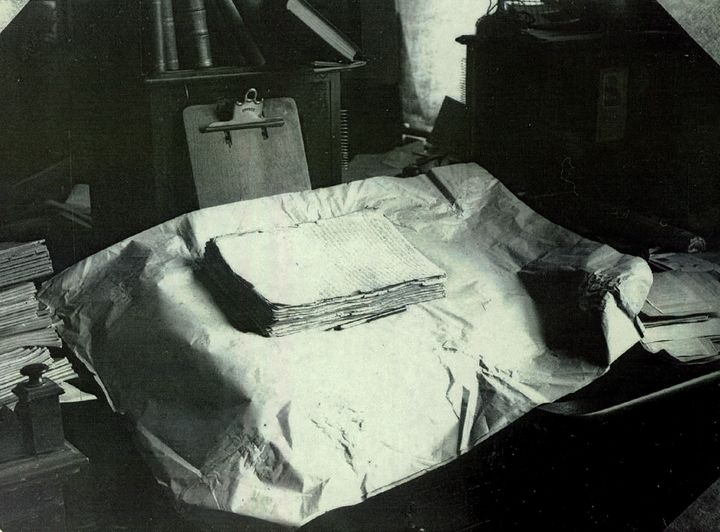 The printer's manuscript of the Book of Mormon rests on a table in this early 20th-century photograph.