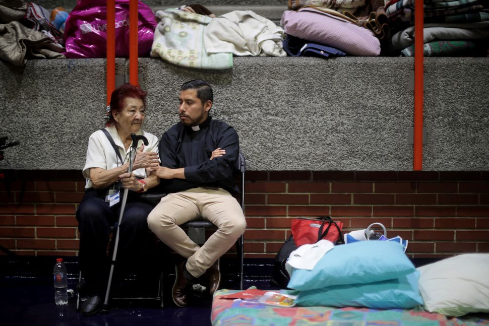 A woman talks with a priest two days after the earthquake in Mexico City, Mexico. The earthquake comes 32 years aft