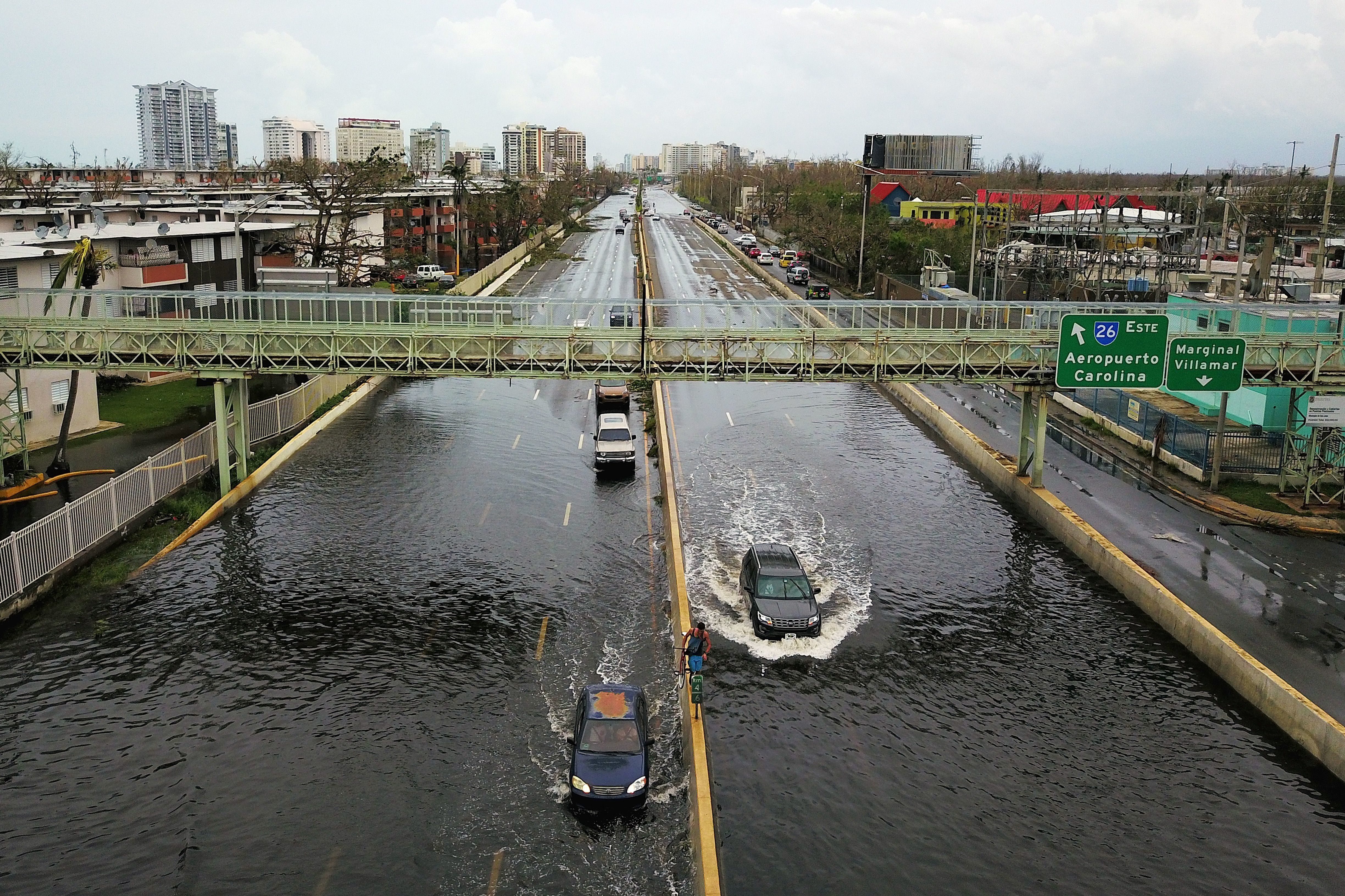 Cars drive through a flooded road in the aftermath of Hurricane Maria in San Juan on Sept. 21,