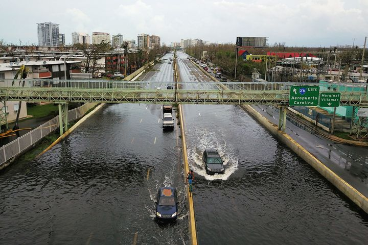 Cars drive through a flooded road in the aftermath of Hurricane Maria in San Juan on Sept.21, 2017.