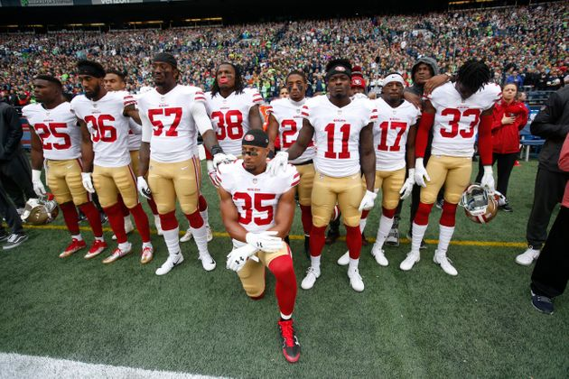 Eric Reid #35 of the San Francisco 49ers kneels during the anthem with the support of teammates prior...