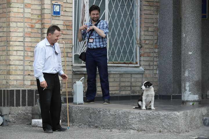 Workers with a stray dog at the Chernobyl nuclear power plant in August 2017.
