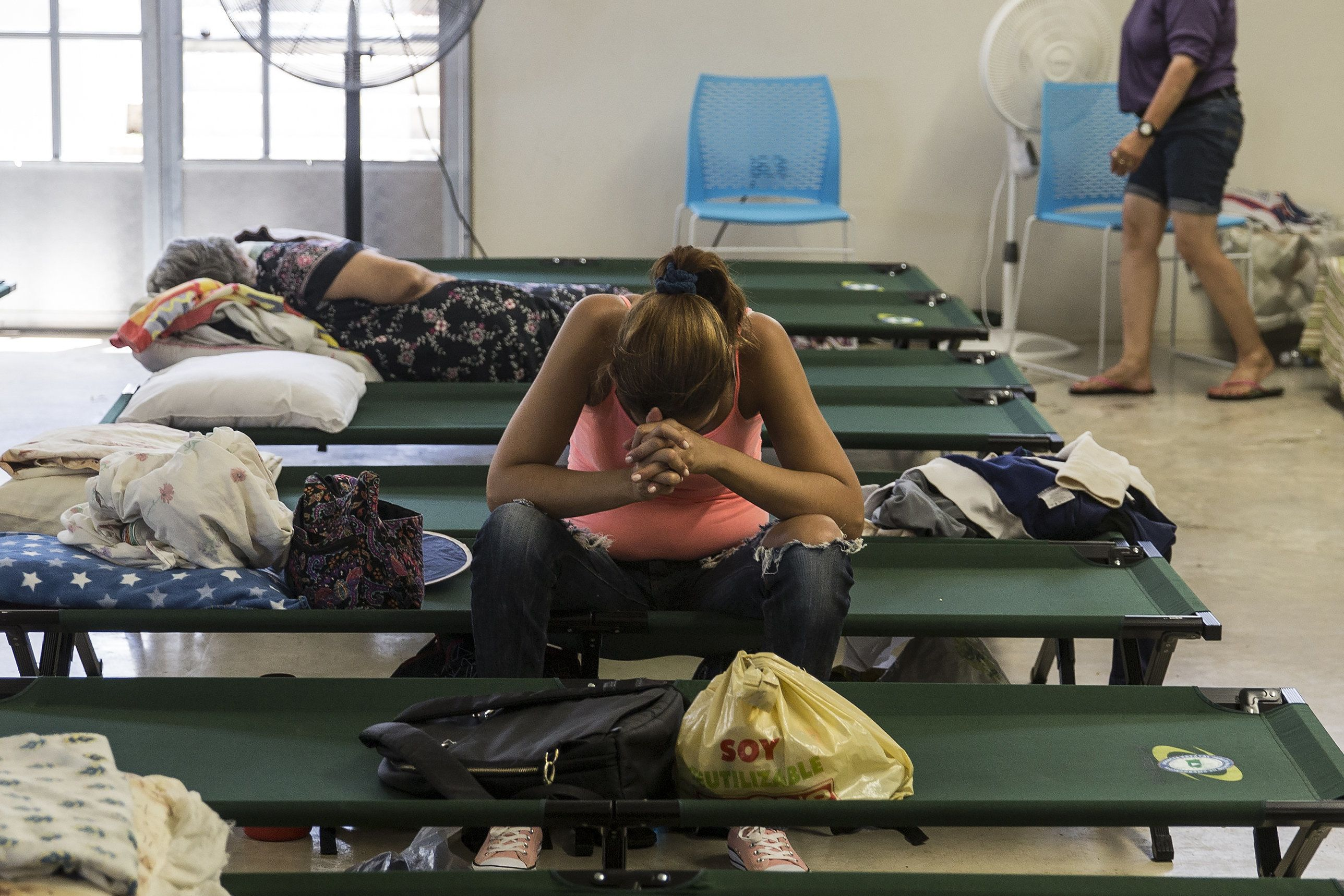 A resident sits inside a shelter after being evacuated from a home near the damaged Guajataca Dam after Hurricane Maria in Isabela, Puerto Rico, on Saturday, Sept. 23, 2017. Amid their struggles to recover from Hurricane Maria, some Puerto Rico residents found it befuddling that President Donald Trump fired off a number of Twitter rants about professional athletes on Saturday -- yet made no mention of their dire situation. Photographer: Alex Wroblewski/Bloomberg via Getty Images