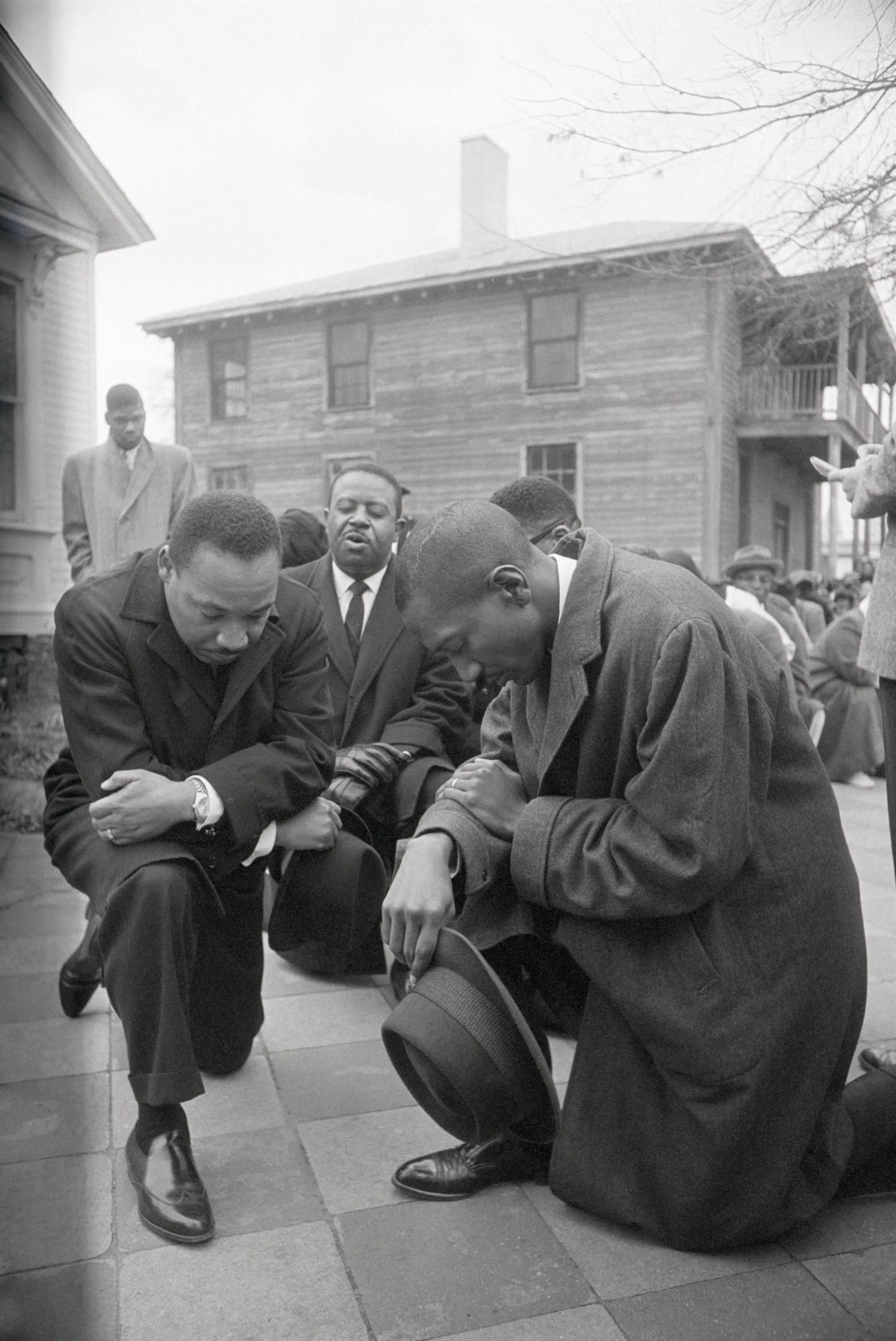 Civil rights leader Martin Luther King Jr. and Ralph Abernathy (center, back) kneel with a group in prayer prior to going to jail in Selma, Alabama. The group was arrested on February 1st after attempting to gain the right to vote. Following the prayer, the group peacefully marched to jail.