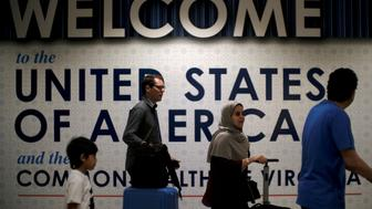 FILE PHOTO: International passengers arrive at Washington Dulles International Airport after the U.S. Supreme Court granted parts of the Trump administration's emergency request to put its travel ban into effect later in the week pending further judicial review, in Dulles, Virginia, U.S., June 26, 2017. REUTERS/James Lawler Duggan/Files