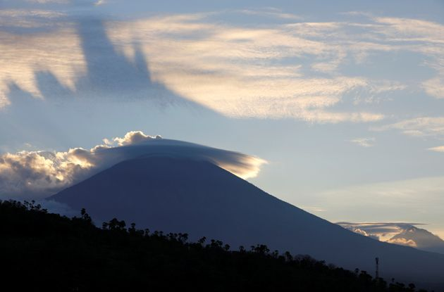 The sun sets behind Mount Agung, a volcano on the highest alert level on the Indonesian island of