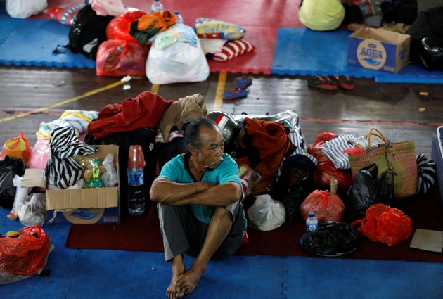 A man rests at a temporary evacuation center for people living near Mount