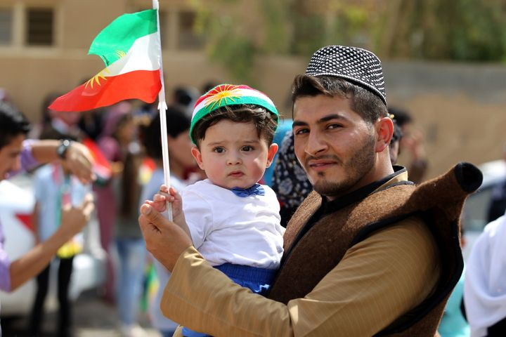 An Iraqi Kurdish man poses as he carries a child wearing the Kurdish flag on his head during a celebration in the northern ci