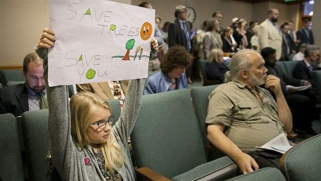 Jayden Malone holds up a sign during a hearing at the Texas Capitol in July on a bill that would have given private property